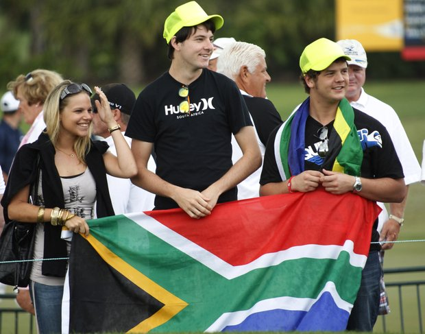 Golf fans holding a South African flag wait at the first tee before Charl Schwartzel tees off during the third round of the Honda Classic.