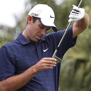 Charl Schwartzel examines a club before teeing off on the first tee during the third round of the Honda Classic.
