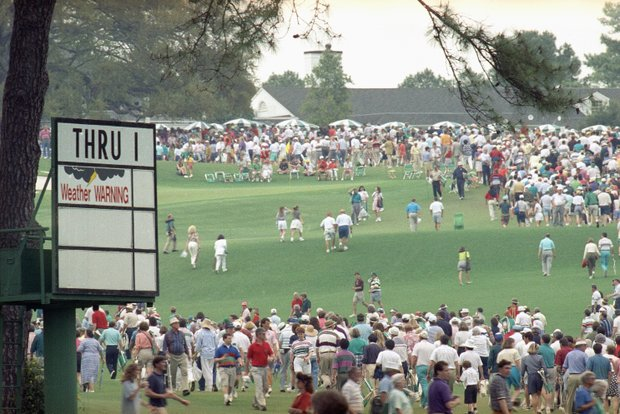 Spectators head for shelter after play was suspended on Saturday, April 11, 1992 during third round play of the Masters at the Augusta National Golf Club in Augusta, Ga. because of bad weather.