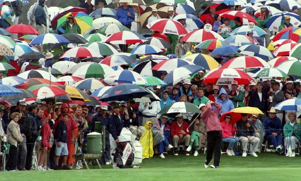 Jack Nicklaus tees off on the third hole amid a sea of umbrellas 09 April 1993 during the second round of the Masters Tournament. Nicklaus was at four-under-par through the tenth hole.
