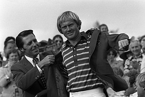 Gary Player, left, defending Masters champion, puts the green jacket on Jack Nicklaus, April 13, 1975, at Augusta National golf club.