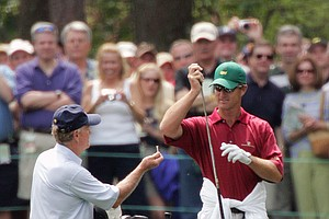 Jack Nicklaus, left, takes the club from his son, caddy Jack Nicklaus II, right, as the younger Nicklaus takes off his caddy coveralls to try and skip the ball on the water on the 16th hole during practice at the Augusta National Golf Club in Augusta, Ga., Wednesday, April 6, 2005.