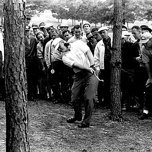 Spectators stand close behind Jack Nicklaus as he hits out of the rough along third fariway during the Masters Golf Tournament at Augusta National Golf Club in Augusta, Ga., April 7, 1962.