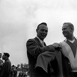 Arnold Palmer, left, 1964 Masters champion helps winner Jack Nicklaus into the traditional green jacket after Nicklaus' nine-stroke victory at Augusta National Golf Club, April 11, 1965.