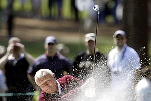 Arnold Palmer, winner of four Masters championships and making his 50th appearance, blasts out of sand bunker at the third green during practice for the Masters golf tournament at the Augusta National Golf Club in Augusta, GA., Tuesday, April 6, 2004.