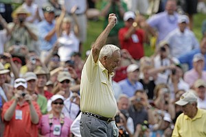 Arnold Palmer celebrates after a birdie putt on the ninth green during the par-3 tournament at the Masters golf tournament in Augusta, Ga., Wednesday, April 7, 2010.