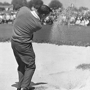 Arnold Palmer lifts from the sand to the 2nd green during Masters Golf Tournament at Augusta, Ga. April 10, 1961. He pitched up for a three foot putt which he sank for a bird. Palmer, defending champion, went into the final round four strokes back of Gary Player.