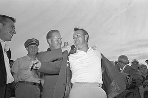 Arnold Palmer slips into a green coat, tradional symbol of the Masters Golf winners, in ceremony at Augusta, Ga April 12, 1964 after a record fourth victory for the Pennsyvania professional.