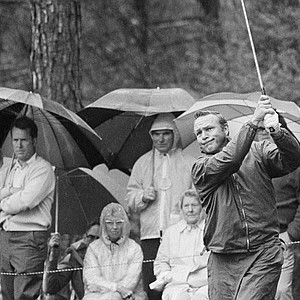 Arnold Palmer, right, watches his drive shot in a drizzling rain during a practice round at the Augusta National Golf Club for the Masters Golf Tournament, Monday, April 6, 1971, Augusta, Ga.