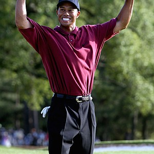 Tiger Woods celebrates his back-to-back Masters win on the 18th hole during the final round of the 2002 Masters, Sunday, April 14, 2002, at the Augusta National Golf Club in Augusta, Ga. Woods won is his third title with a 12-under-par 276 for the tournament.