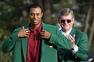 "Tiger Woods, left, adjusts the 2002 Masters green jacket as Augusta National Golf Club chairman William W.""Hootie"" Johnson applauds at the Augusta National Golf Club in Augusta, Ga."