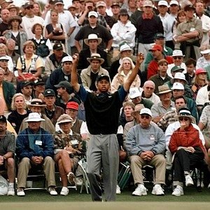 Tiger Woods stretches before his putt on the 18th green during second round Masters play at the Augusta National Golf Club in Augusta, Ga., Friday, April 11, 1997. Woods shot a 66 to take the lead in the trounament.