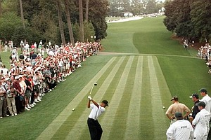Surrounded by the gallery, defending Masters champion Tiger Woods drives off of the 18th tee during the final day of practice for the 1998 Masters at the Augusta National Golf Club in Augusta, Ga., Wednesday, April 8, 1998.