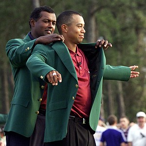 Tiger Woods, right, receives his Masters green jacket from champion Vijay Singh, of Fiji, after winning the 2001 Masters at the Augusta National Golf Club in Augusta, Ga.