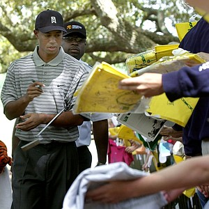 Defending Masters Champion Tiger Woods signs autographs as he leaves the driving range at the Augusta National Golf Club during the first practice round for the 2002 Masters, Monday, April 8, 2002, in Augusta, Ga.