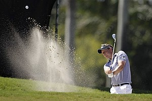 Luke Donald, of England, hits from a bunker onto the first green during the final round at the Cadillac Championship.
