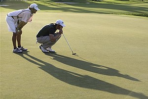 Nick Watney, right, lines up a putt on the 18th green with his caddy Chad Reynolds, left, during the final round at the Cadillac Championship in Doral, Fla., Sunday, March 13, 2011.
