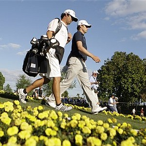 Nick Watney, right, walks with his caddy Chad Reynolds, left, from the 15th tee during the final round at the Cadillac Championship in Doral, Fla.