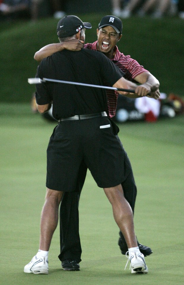 Tiger Woods, right, celebrates with caddie Steve Williams after sinking the putt to win the Arnold Palmer Invitational golf tournament at Bay Hill in Orlando, Fla., Sunday, March 29, 2009.