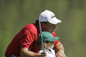 Phil Mickelson sits with his five-year-old son Evan on the third green during the par three tournament prior to the 2008 Masters golf tournament at the Augusta National Golf Club in Augusta, Ga., Wednesday, April 9, 2008.