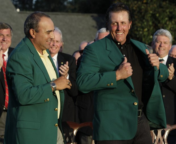 Former Master's champion Angel Cabrera, left, of Argentina helps Phil Mickelson put on his Masters jacket after his win at the 2010 Masters golf tournament in Augusta, Ga., Sunday, April 11, 2010.
