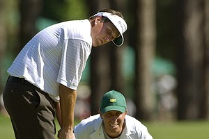 Phil Mickelson, left, is joined by caddie Jim MacKay as he takes a read on his putt on the eighth hole in the third round at the 2003 Masters at the Augusta National Golf Club in Augusta, Ga., Saturday, April 12, 2003.