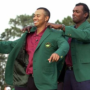Tiger Woods, left, receives his Masters green jacket from last year's champion Vijay Singh of Fiji, after winning the 2001 Masters at the Augusta National Golf Club in Augusta, Ga., Sunday, April 8, 2001. Woods captured this second Masters title, defeating David Duval by two stokes.