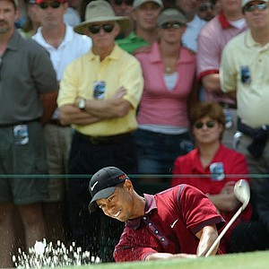 Tiger Woods chips out of a sand trap on the first fairway during the final round of the Masters golf tournament.