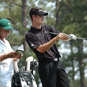 Justin Rose plans his shot on the second fairway with his caddie Philip Morbey during the final round of the Masters golf tournament at the Augusta National Golf Club.