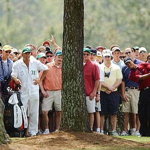 Tiger Woods chips from behind trees on the first fairway during the final round of the Masters golf tournament.