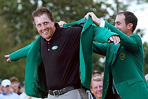 Mike Weir puts the 2004 Master green jacket on winner Phil Michelson. Mickelson won the Masters with a nine-under-par.