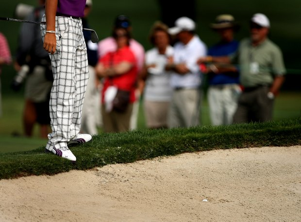 Rickie Fowler looks over his buried lie at No. 3, in a greenside bunker, during Round 1 of the Arnold Palmer Invitational at Bay Hill Club & Lodge.