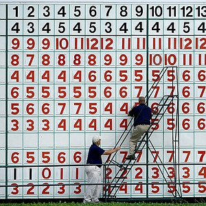 Volunteers work to change scores at the leaderboard at No. 18.