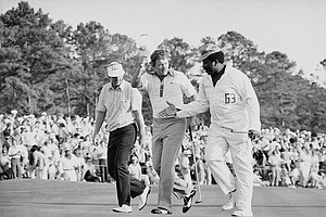 Golfer Ray Floyd, center, doffs his visor as caddie Hop Harris reaches over to shake hands after Floyd won the Masters Championship on Sunday, April 11, 1976 at Augusta, Ga.