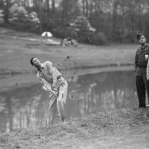 Charlie Coe makes a splash as he drives his ball from the mud at the edge of a lake bordering the 15th green, during second round of the Masters Golf Tournament at Augusta, Ga., April 6, 1951.