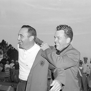 Masters Tournament golf champ Doug Ford, left, gets assistance from Jack Burke Jr., as he slips into the traditional green jacket worn only by tournament winners, Augusta, Ga., April 8, 1957.
