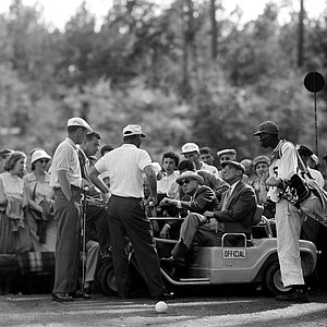 Arnold Palmer, center standing, argues a rules point at the 12th hole after his ball became embedded in the mud during final round of the Masters Golf Tournament at Augusta National Golf Club in August, Ga., April 6, 1958. The final ruling gave the 28-year-old Palmer, of Latrobe, Pa., a three on the hole and a 73 round for a 284 total.