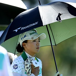Chie Arimura keeps cool with an umbrella and cold compress during the second round.
