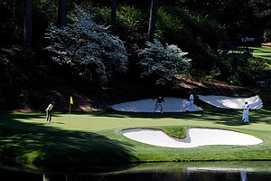 Hiroyuki Fujita, right, and Ryo Ishikawa wait with their caddies on the 12th green during a practice round prior to the 2011 Masters.