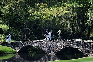 Hiroyuki Fujita, left, and Ryo Ishikawa cross the Nelson Bridge with their caddies during a practice round prior to the 2011 Masters.