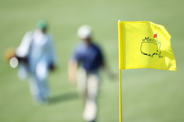 A Masters flagstick is seen as a player and caddie approach a green during a practice round prior to the 2011 Masters Tournament at Augusta National Golf Club on April 4, 2011 in Augusta, Georgia.
