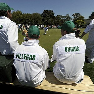 Caddies are gathered around the putting green during a practice round prior to the 2011 Masters Tournament at Augusta National Golf Club April 4, 2011 in Augusta, Georgia.