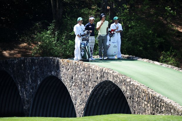 Hiroyuki Fujita (L) and Ryo Ishikawa of Japan pose with their caddies on the Hogan Bridge during a practice round prior to the 2011 Masters Tournament at Augusta National Golf Club on April 4, 2011 in Augusta, Georgia.