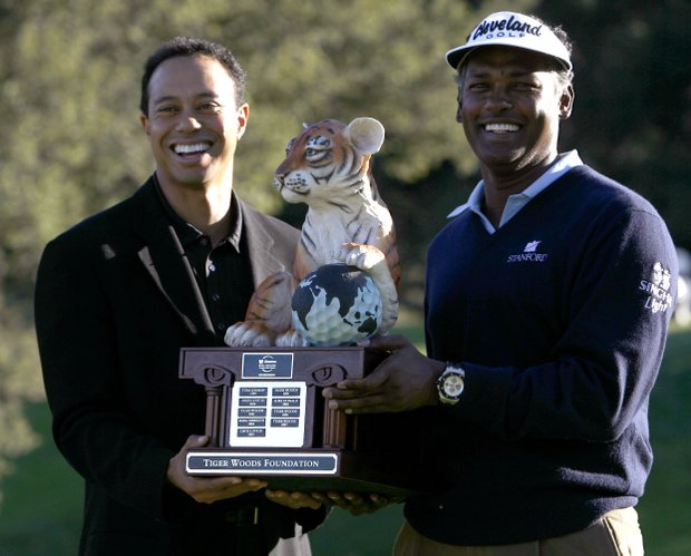 Vijay Singh, of Fiji, holds the trophy as he poses with tournament host Tiger Woods after Singh won the Chevron World Challenge golf tournament at Sherwood Country Club in Thousand Oaks, Calif., Sunday, Dec. 21, 2008.