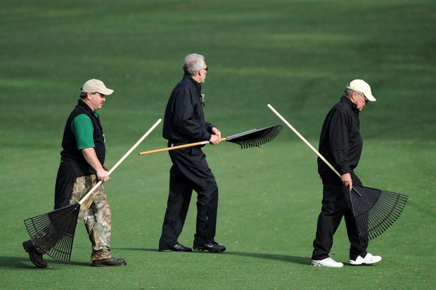 Members of the grounds staff walk across a fairway during a practice round prior to the 2011 Masters.