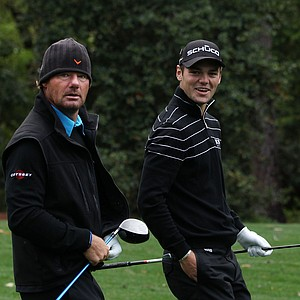 Alex Cekja, left, and Martin Kaymer of Germany walk down a fairway during a practice round prior to the 2011 Masters.