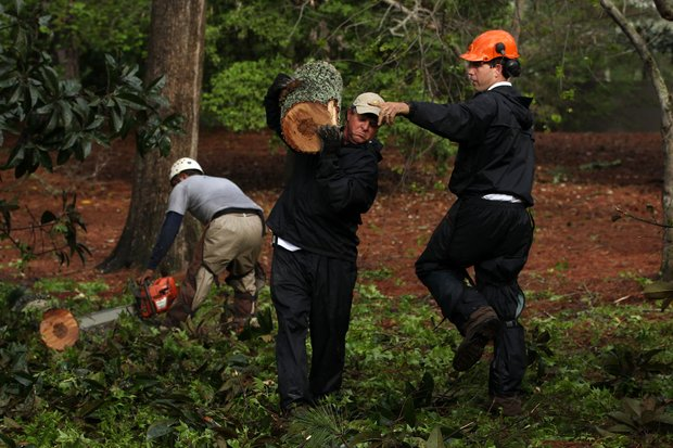 Members of the grounds staff clear debris from the course after an overnight storm prior to the 2011 Masters.