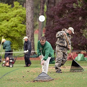 Course workers rake debris from the eighth fairway during a practice round prior to the 2011 Masters Tournament. A storm that passed through the area overnight caused damage and delayed tee times on the course.