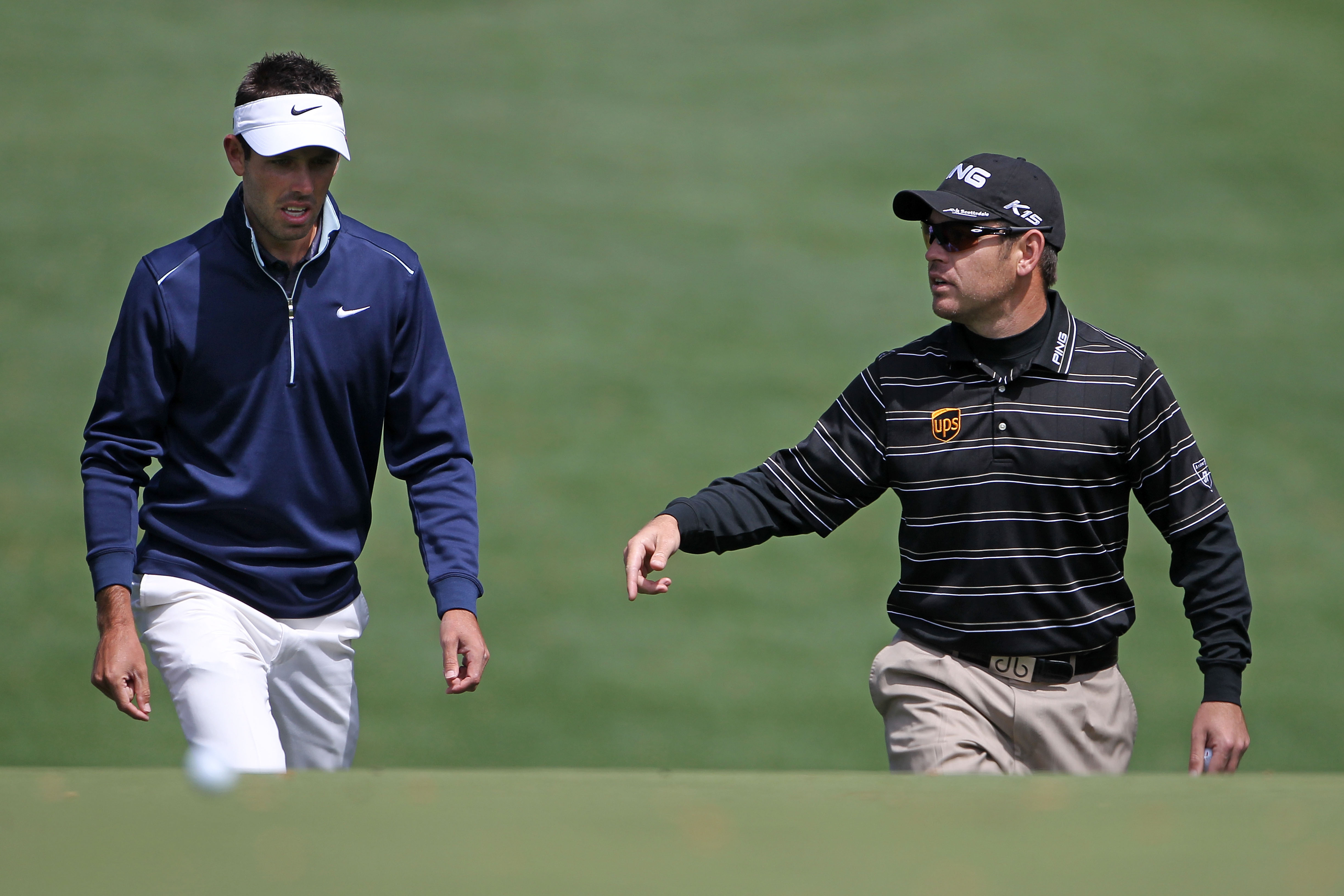 Charl Schwartzel (L) and Louis Oosthuizen of South Africa walk to a green during a practice round prior to the 2011 Masters Tournament at Augusta National Golf Club on April 5, 2011 in Augusta, Georgia.