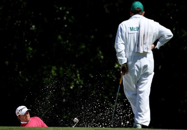 Graeme McDowell of Northern Ireland plays a bunker shot as his caddie Ken Comboy looks on during a practice round prior to the 2011 Masters Tournament at Augusta National Golf Club on April 5, 2011 in Augusta, Georgia.